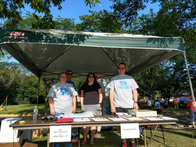 Tour de Potsdam 2018 volunteers stand behind the registration table under the shade of a canopy tent