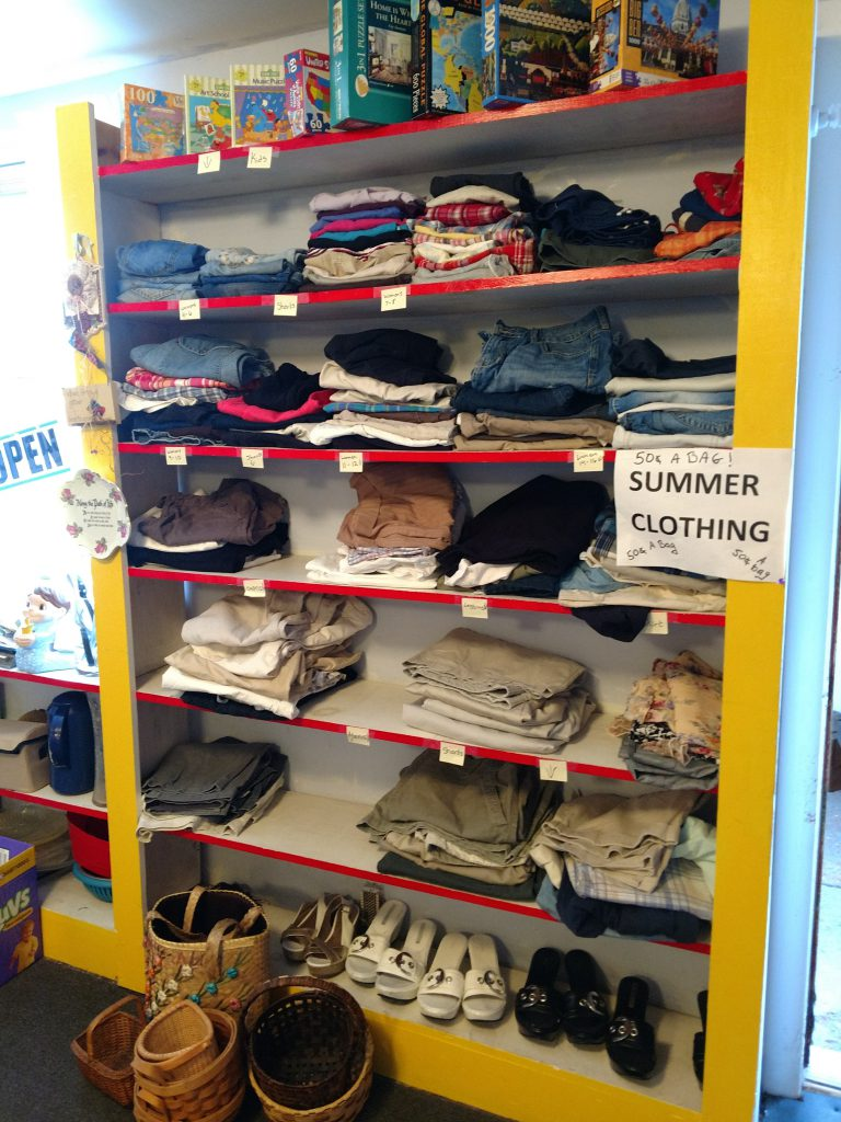 A shelf of summer clothing and shoes available at a neighorhood center