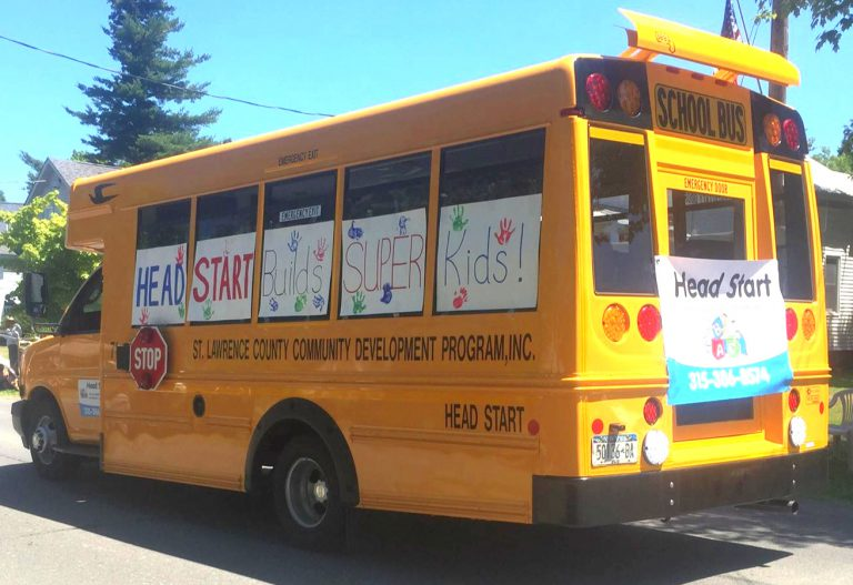 Yellow school bus with hand-made Headstart signs stuck on the windows