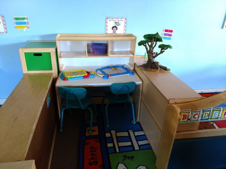 Study desk for two with two magnetic drawing boards and a plastic tree sculpture on top at a HeadStart center