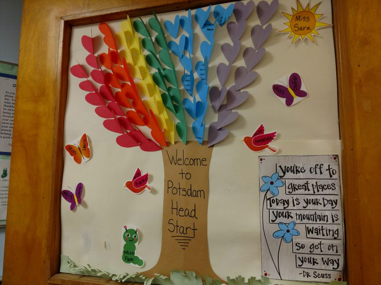 Potsdam Head Start welcome board with colorful pieces of paper used to create a rainbow tree surrounded by birds and butterflies and a Dr. Suess inspirational quote beside it