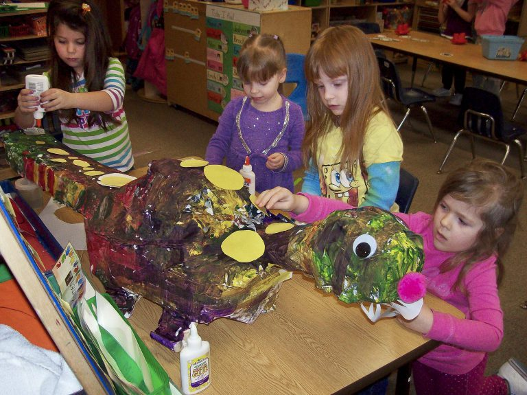 Four brown-haired girls work on a crafts project, making a turtle-like animal sculpture