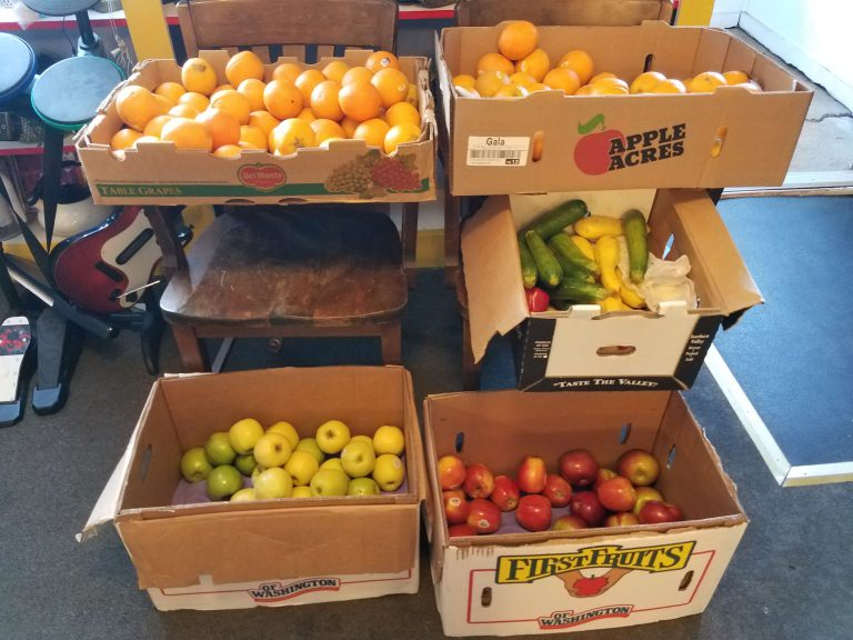 Boxes of apples, oranges and squash at a neighborhood center