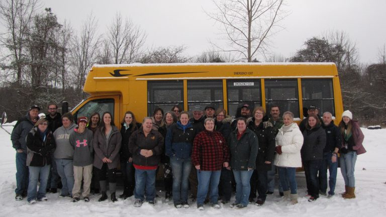 Head Start transportation staff and the Head Start director pose in front of a yellow school bus in the winter time