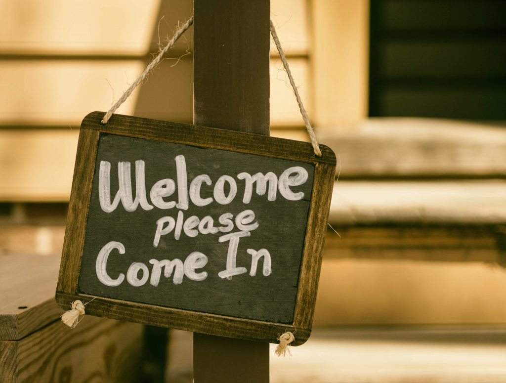 "A chalk board hung up with the words ""Welcome please come in"""
