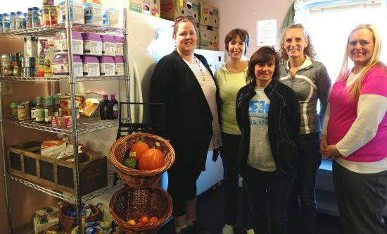 Neighborhood center directors take a photo together at a neighborhood center beside shelves of foodstuff