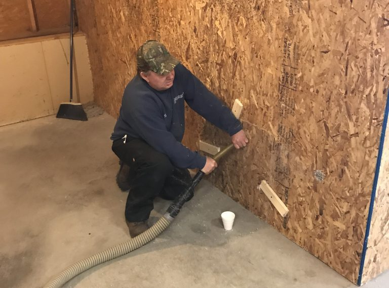 Weatherization employee kneeling in front of a wall working on its insulation